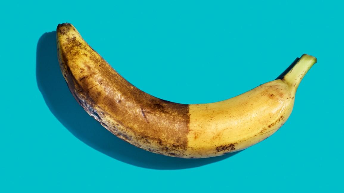 banana amarela com casca marrom escurecida gradualmente na metade inferior