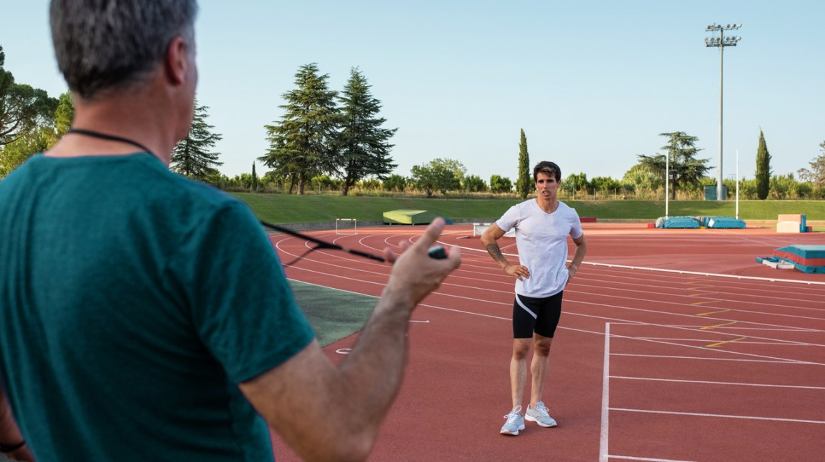 father coaching son on athletic track