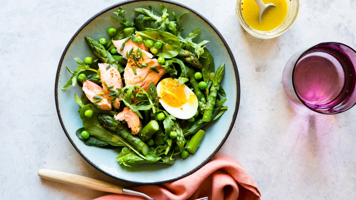 salad made of spinach, salmon, egg, peas, and asparagus next to a fork, cloth napkin, and glasses of salad dressing and water