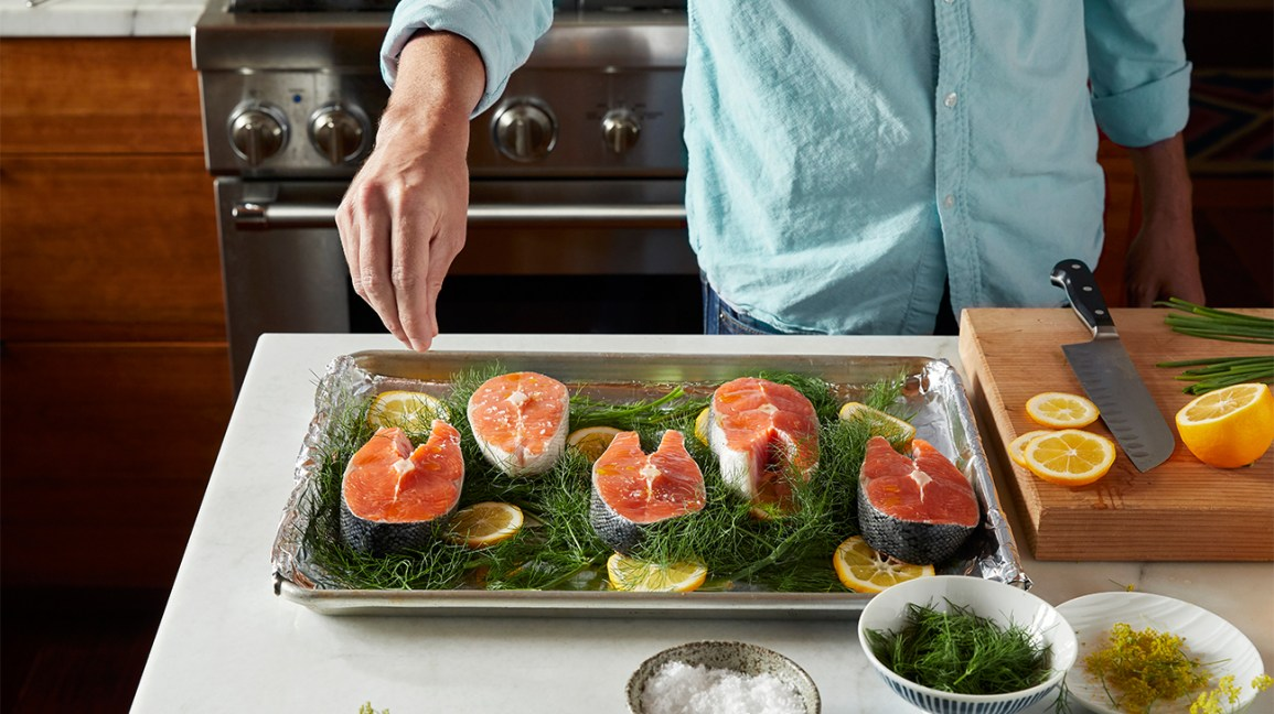 man sprinkling spices on raw salmon in baking tray