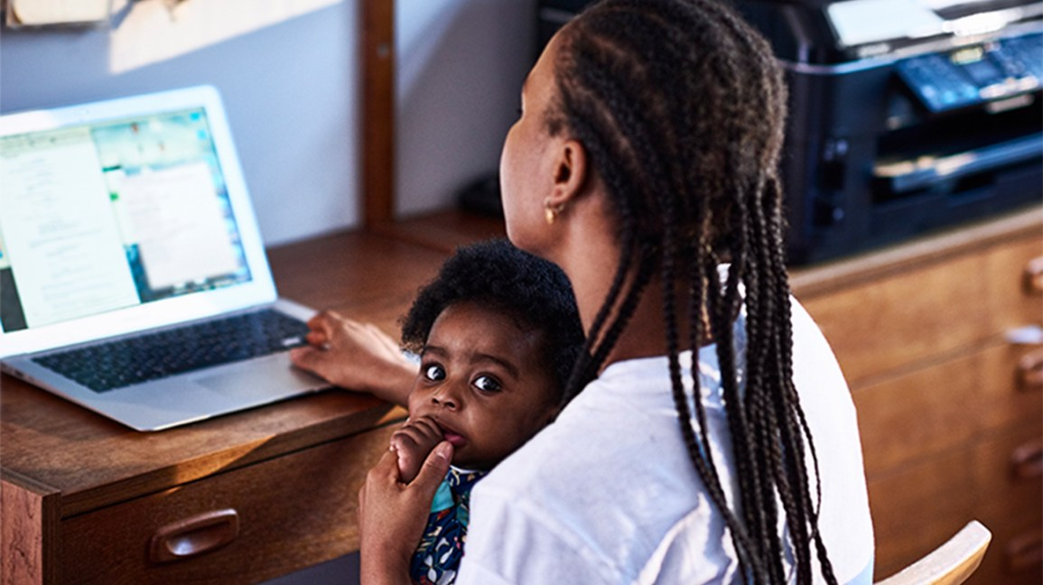 mother working on laptop with baby on her lap