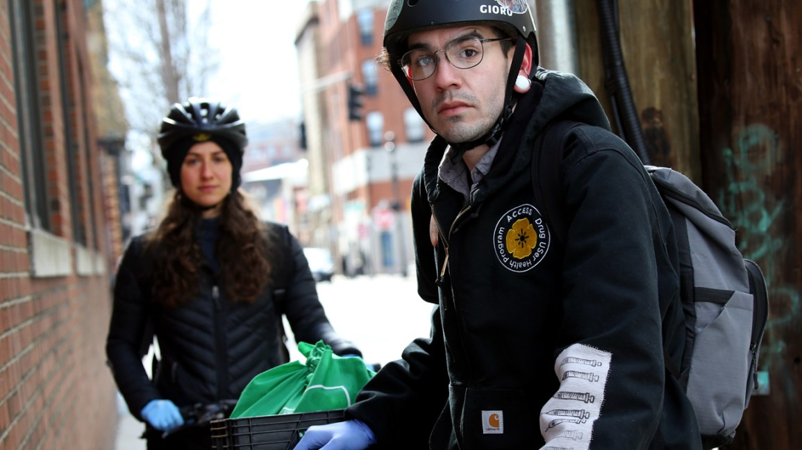 man and woman on bike with narcan supplies