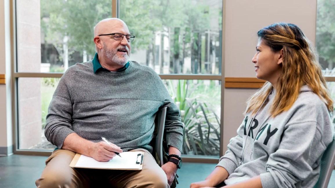 Uma mulher está sentada em uma sala conversando com seu terapeuta.