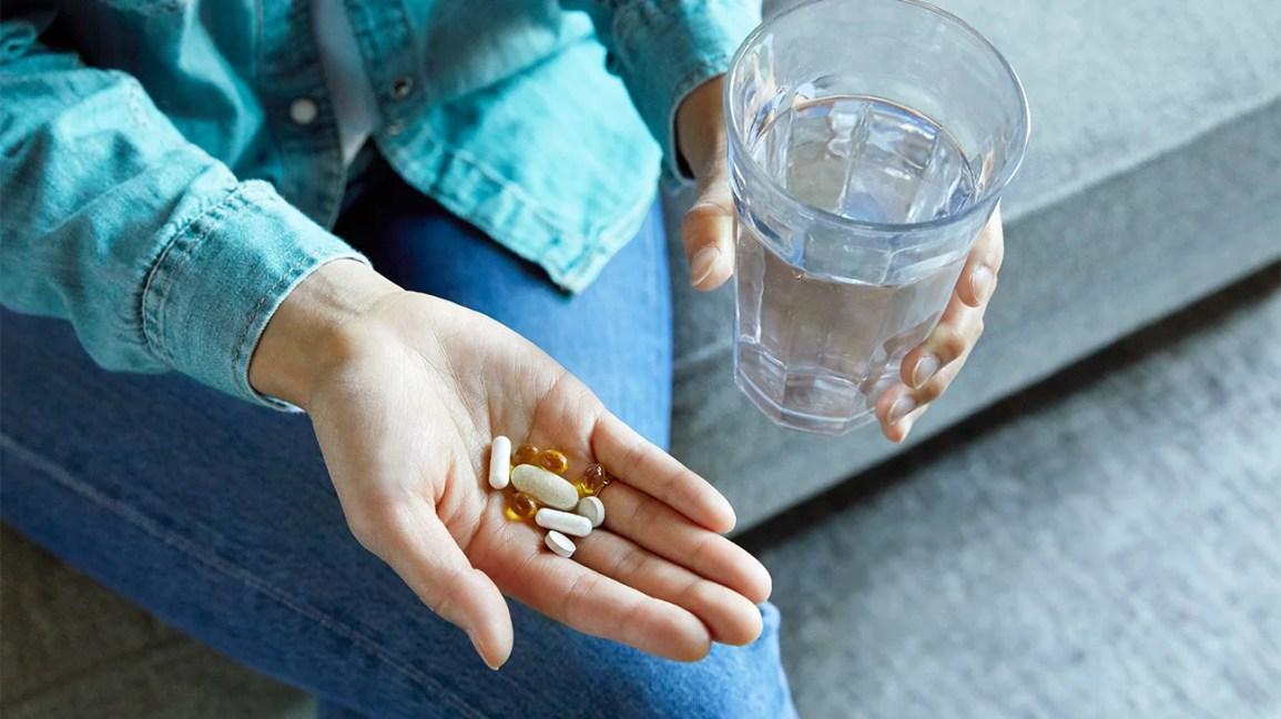 Добавки в руку со стаканом воды