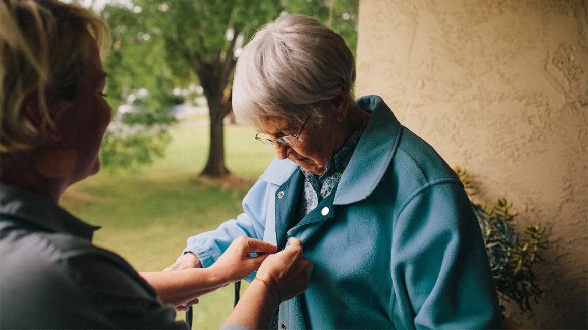 Um profissional de saúde ajuda um adulto mais velho a abotoar sua jaqueta.