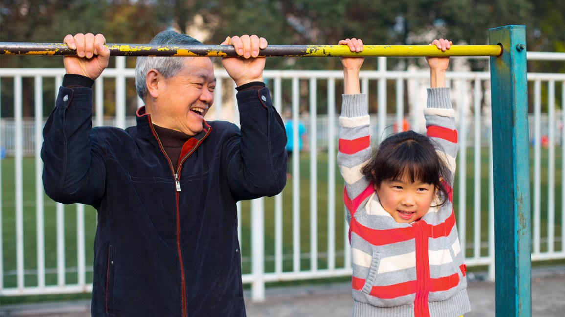 Senior and child hanging from pull up bar