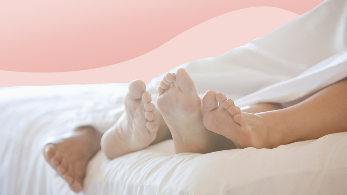 Two people's feet in bed