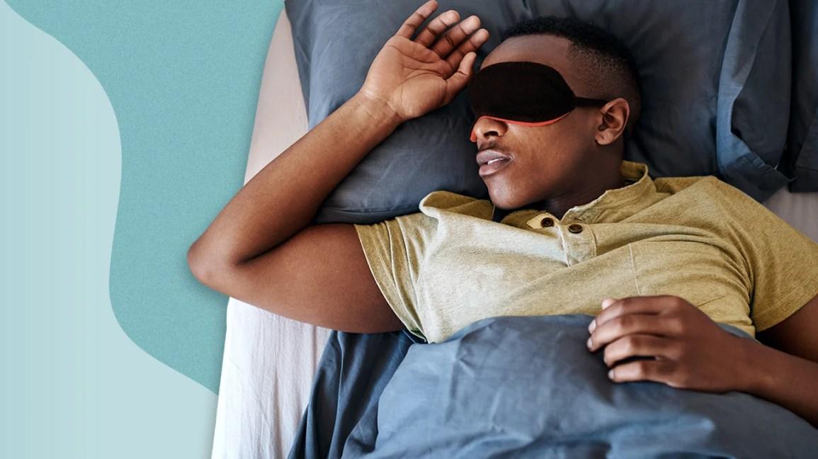 yatakta göz maskesi ile uyuyan adam