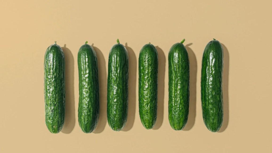 sei cetrioli verdi di dimensioni e forma simili in fila su uno sfondo beige