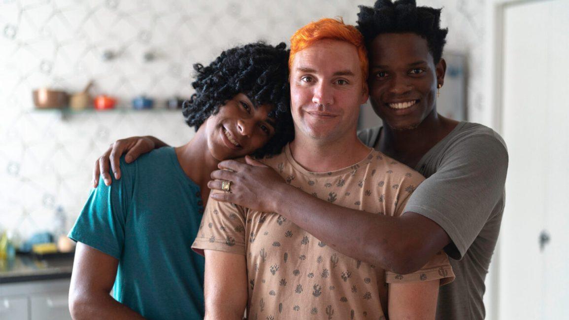 ritratto di tre persone in piedi con le braccia intorno a vicenda, sorridendo alla telecamera