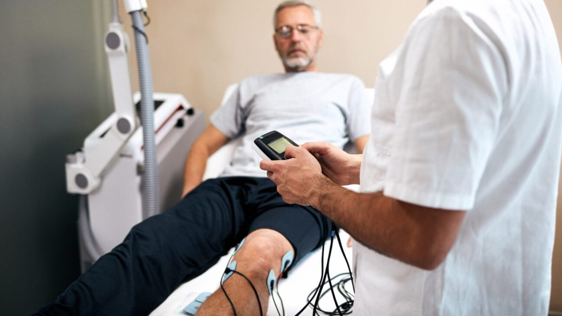 Um paciente deita-se em uma cama com almofadas TENS fixadas na parte inferior da perna.