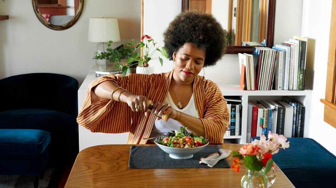 woman cracking pepper over a salad at home