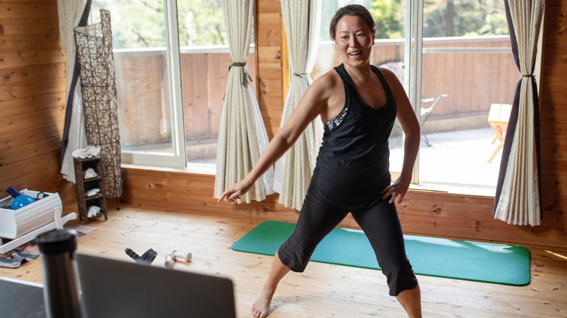 woman doing exercises at home in front of computer