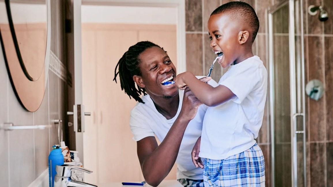 Bir adam ve oğlu banyoda birlikte dişlerini fırçalar.