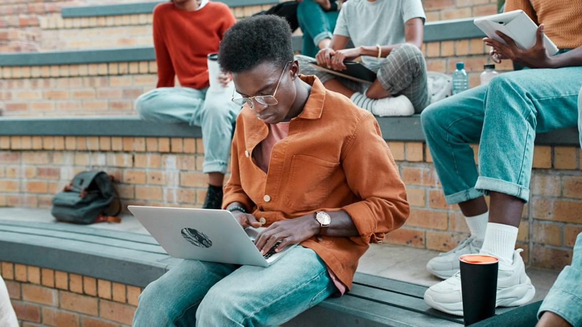Um jovem se senta ao ar livre, trabalhando em seu laptop em uma reunião social.