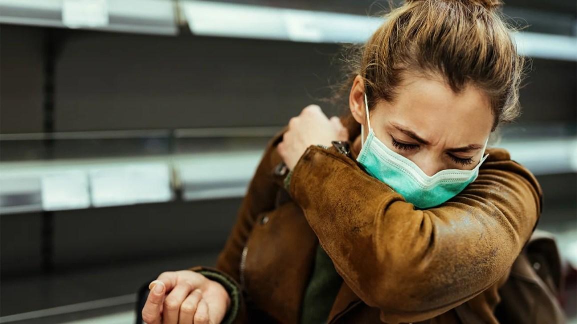 espirrando no cotovelo, mulher usando uma máscara facial vendo seu cotovelo