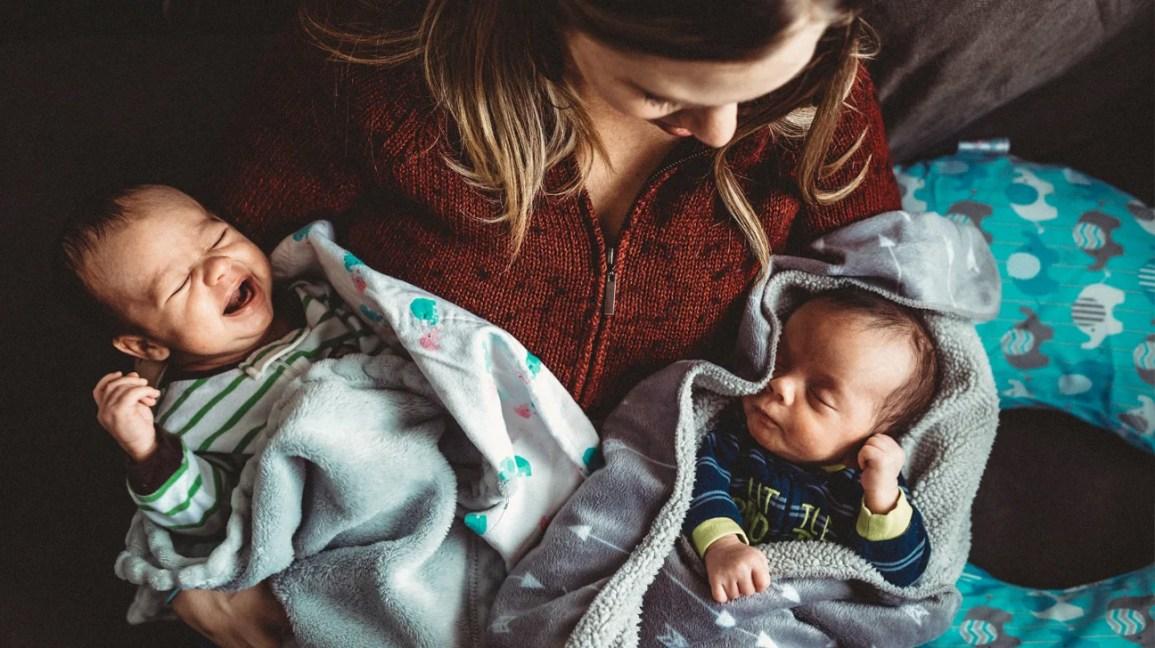 Mulher segurando gêmeos recém-nascidos