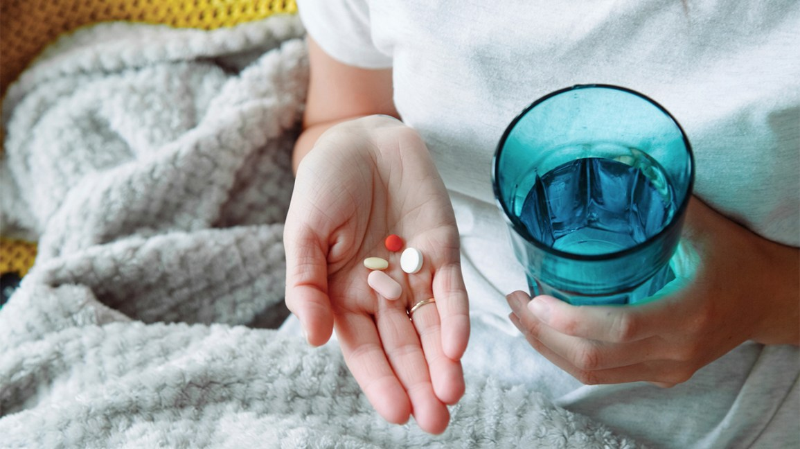 Person taking vitamins with a glass of water