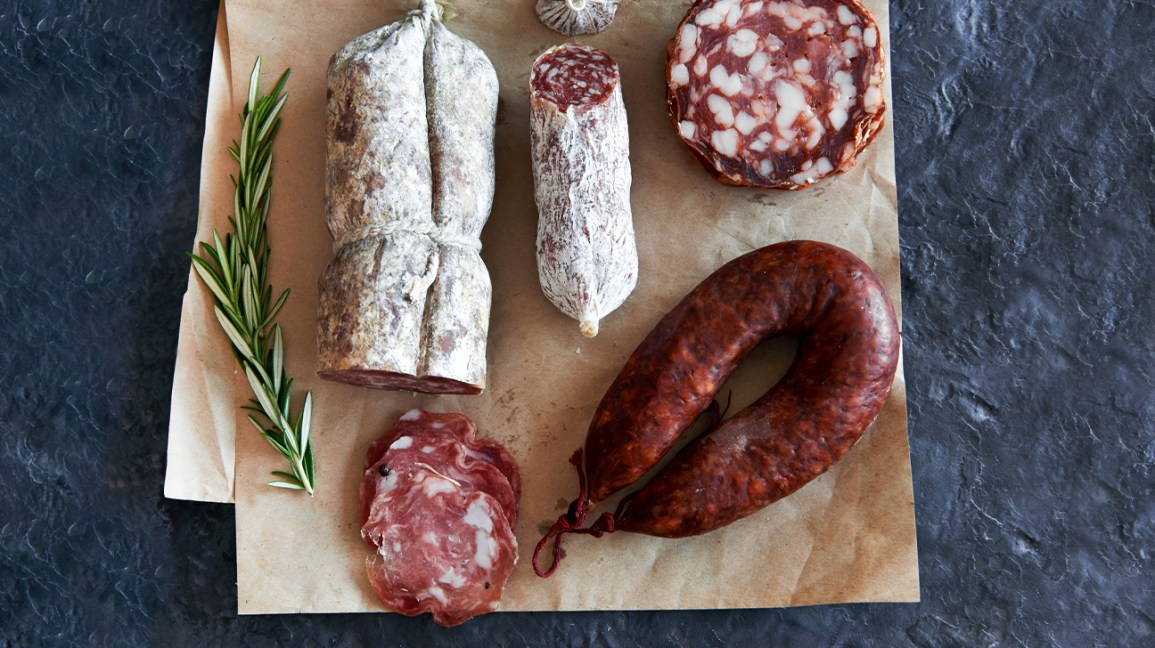 Sausages and salamis on a cutting board