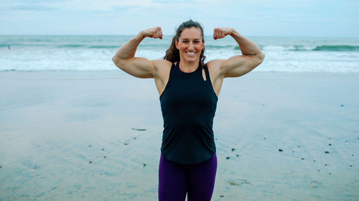 Woman flexing her muscles at the beach