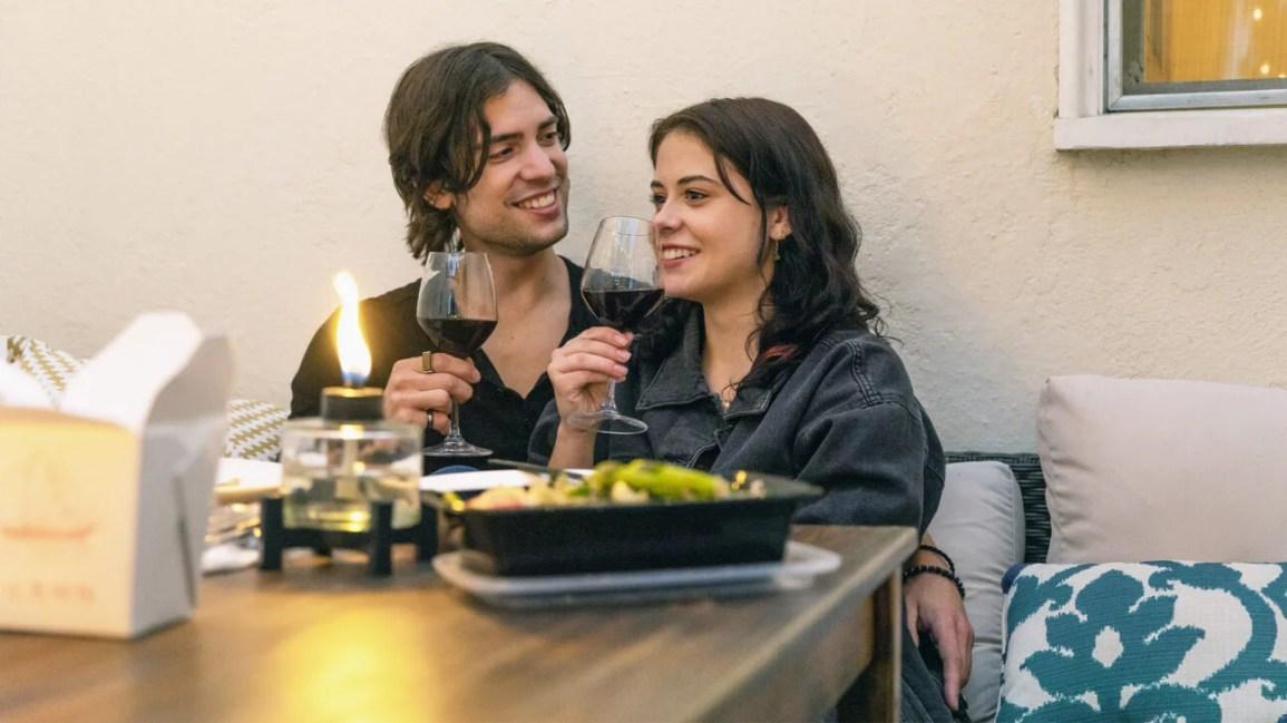 casal sentado junto à mesa de jantar comendo comida para fora