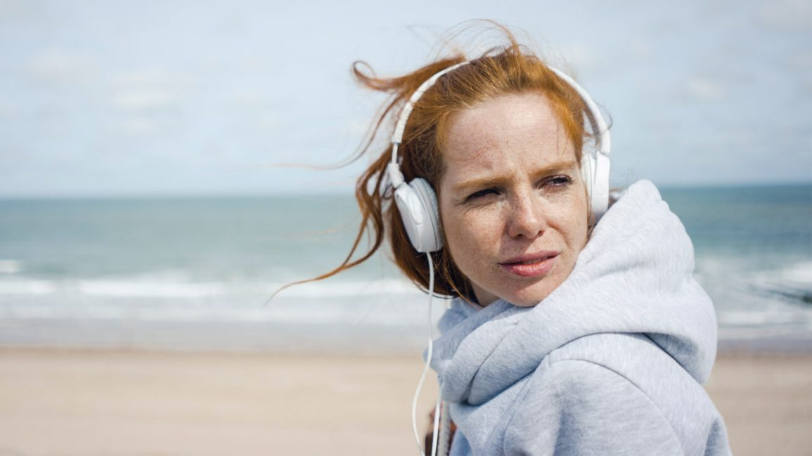 woman on the beach wearing headphones