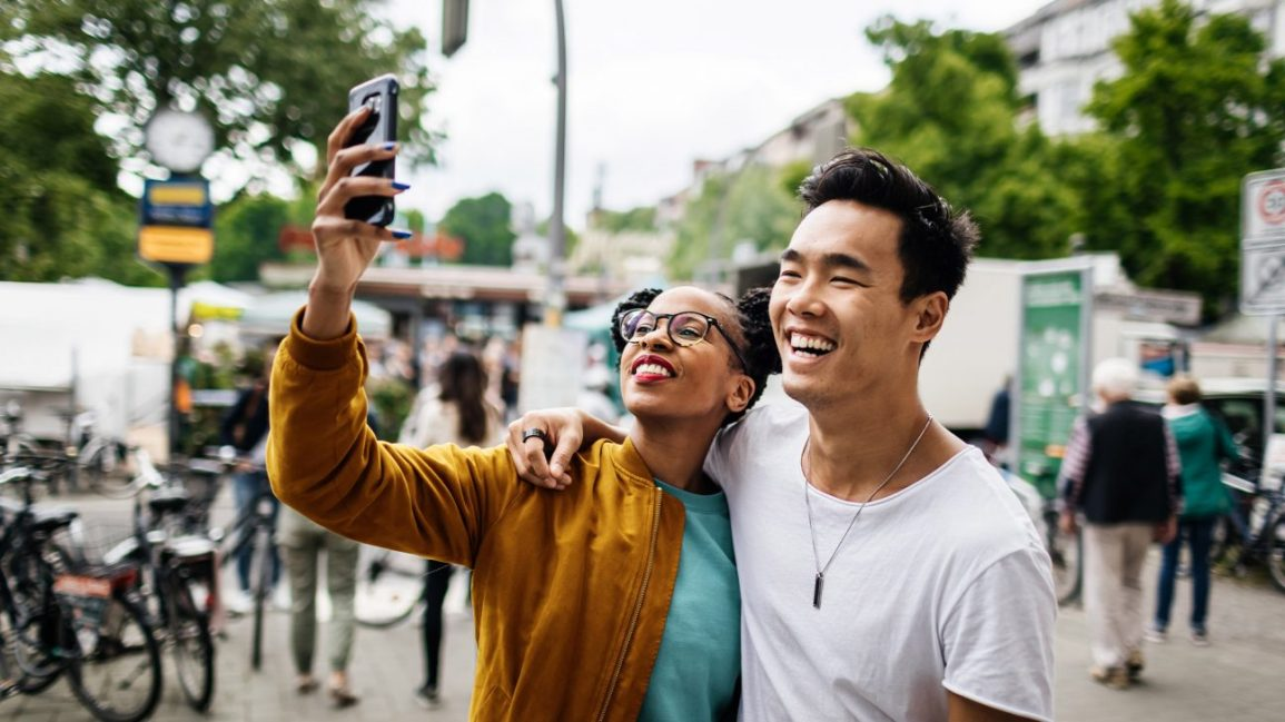 couple taking a selfie together at the park; the person on the left is wearing glasses, a blue t-shirt, and a mustard jacket, and the person on the right is wearing a white tee shirt and long silver necklace