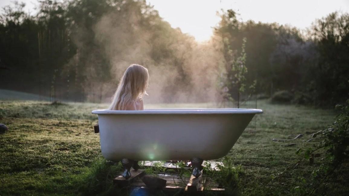 imagem de uma pessoa sentada em uma banheira fumegante em um gramado verde