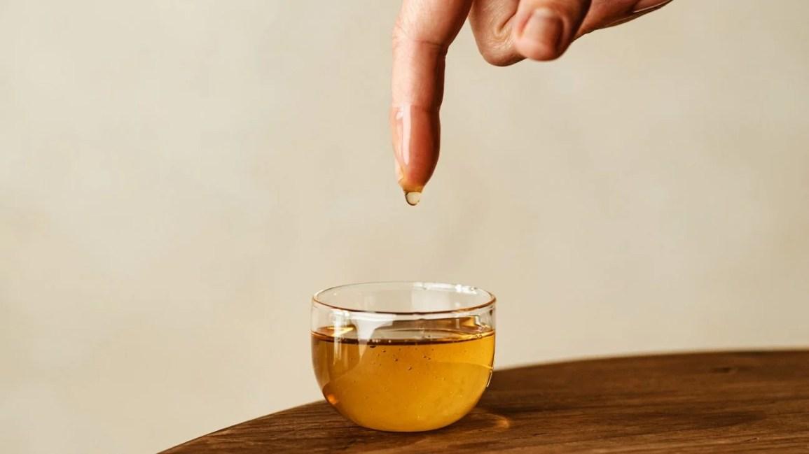 imagem de uma pessoa mergulhando o dedo em uma xícara de chá preto transparente