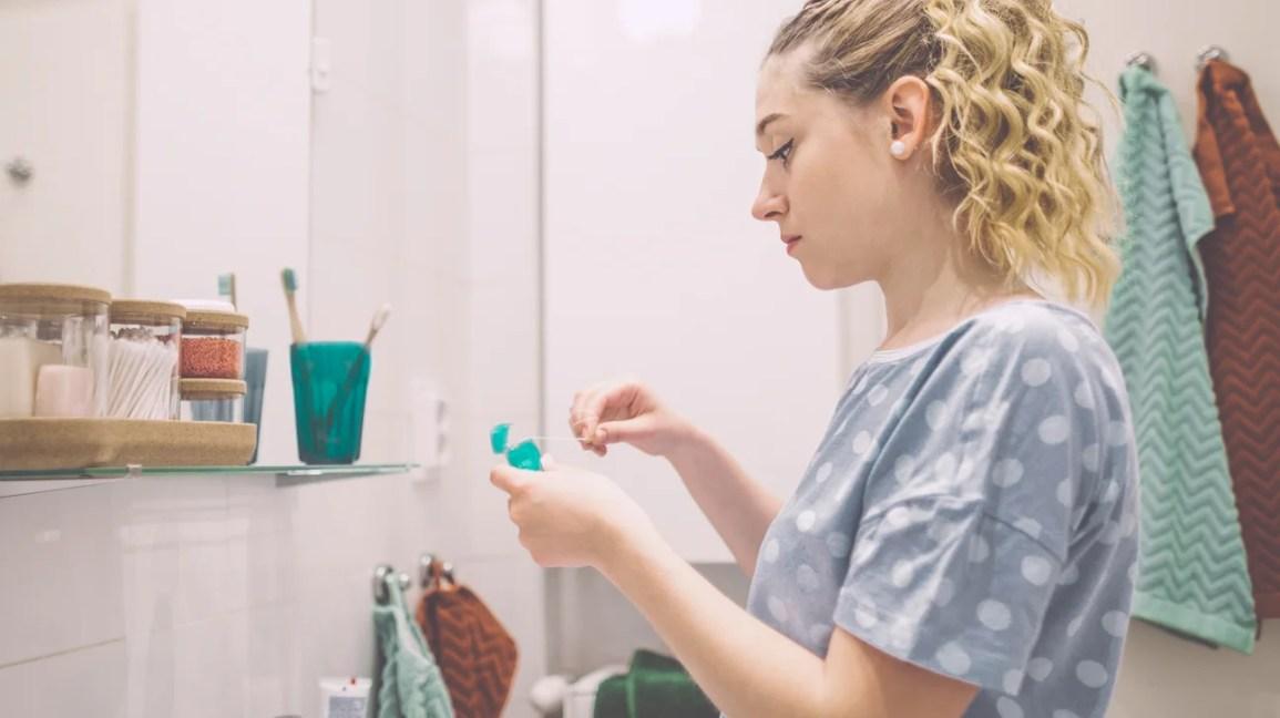 Una donna sta davanti allo specchio del bagno mentre tira un pezzo di filo interdentale da un distributore di filo interdentale.