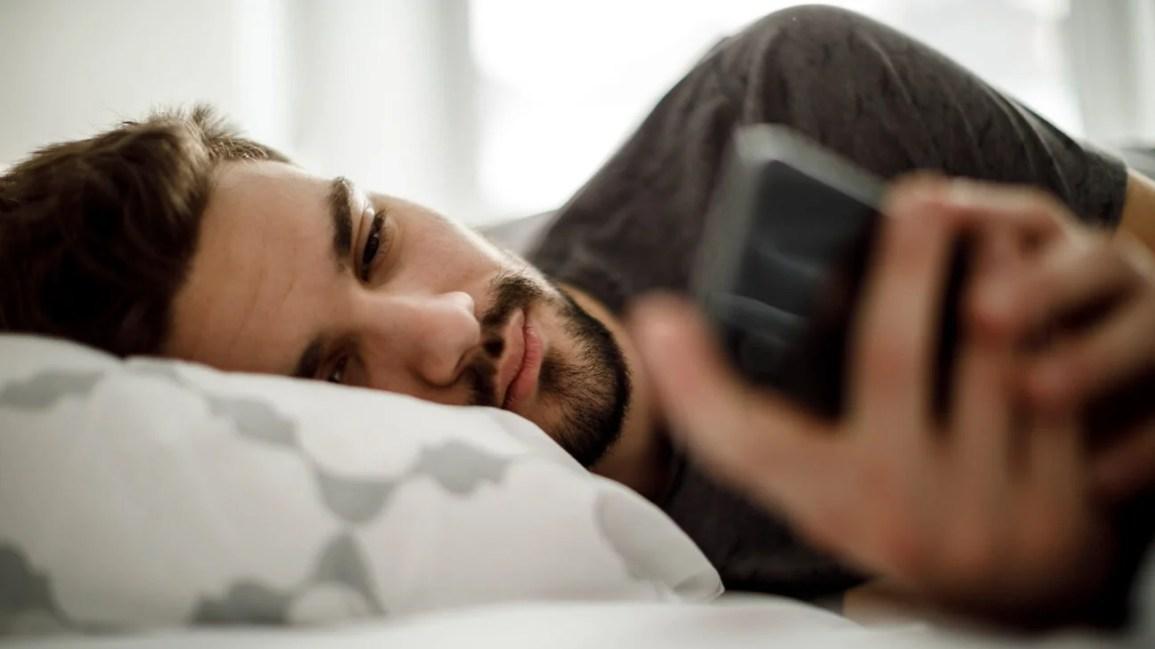 homem deitado de lado enviando mensagens de texto na cama