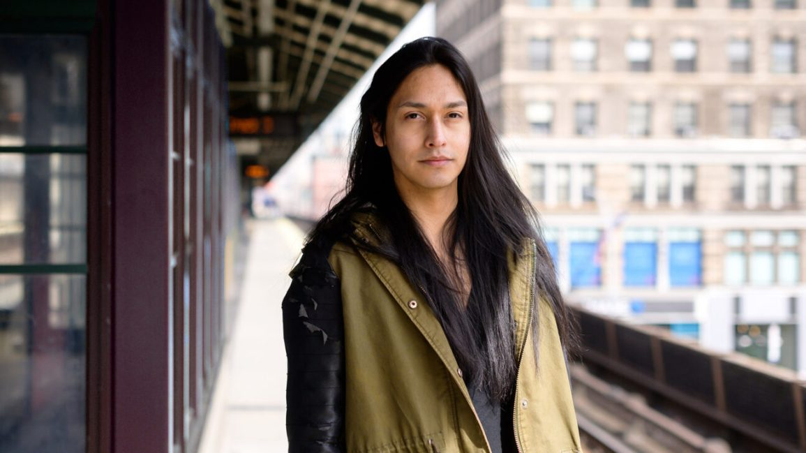 native american man standing on subway platform