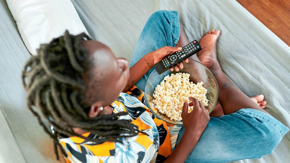 Você pode comer pipoca com aparelho, mulher no sofá com tigela de pipoca