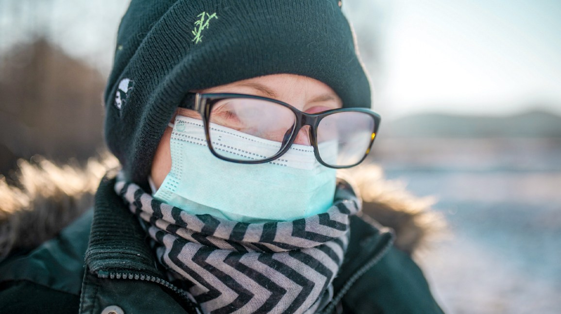 A woman wears a face mask and warm winter clothes, with fog on the inside of her glasses.