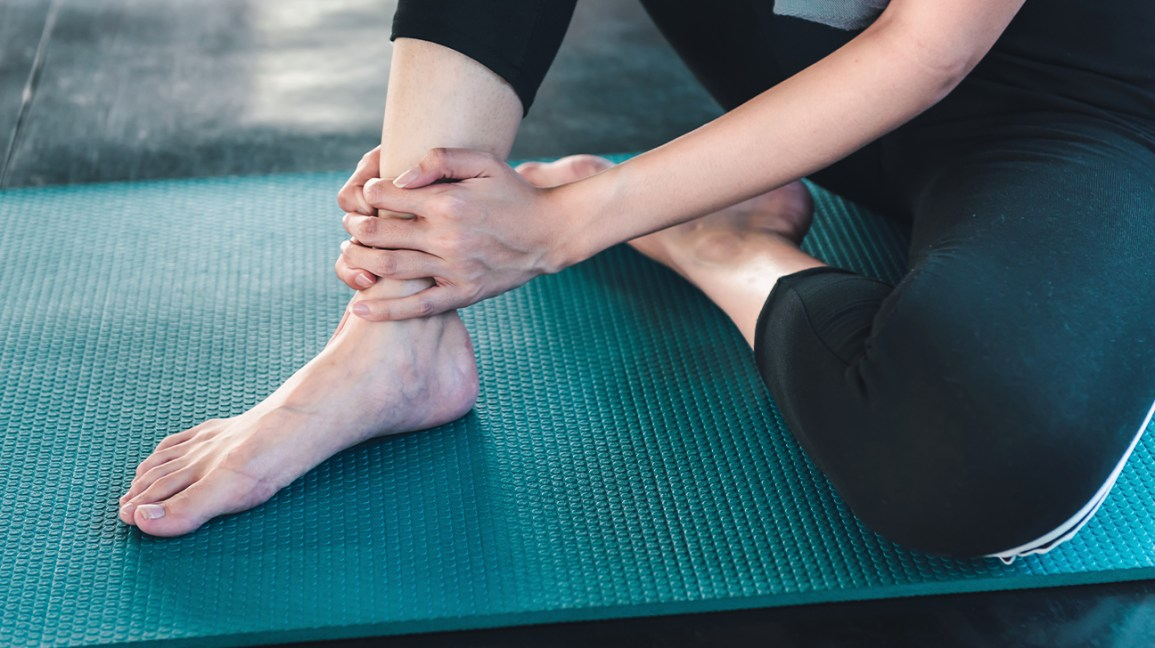A person sits on an exercise mat while holding their injured ankle.