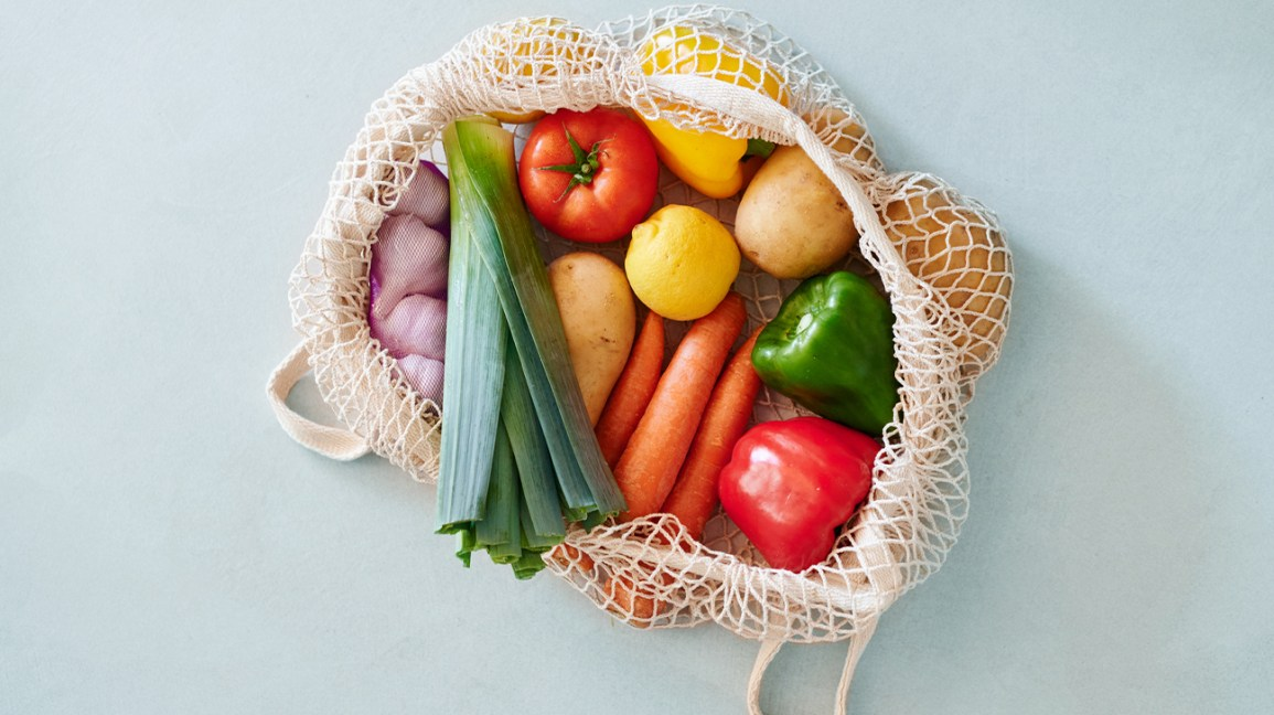reusable grocery bag filled with fresh vegetables