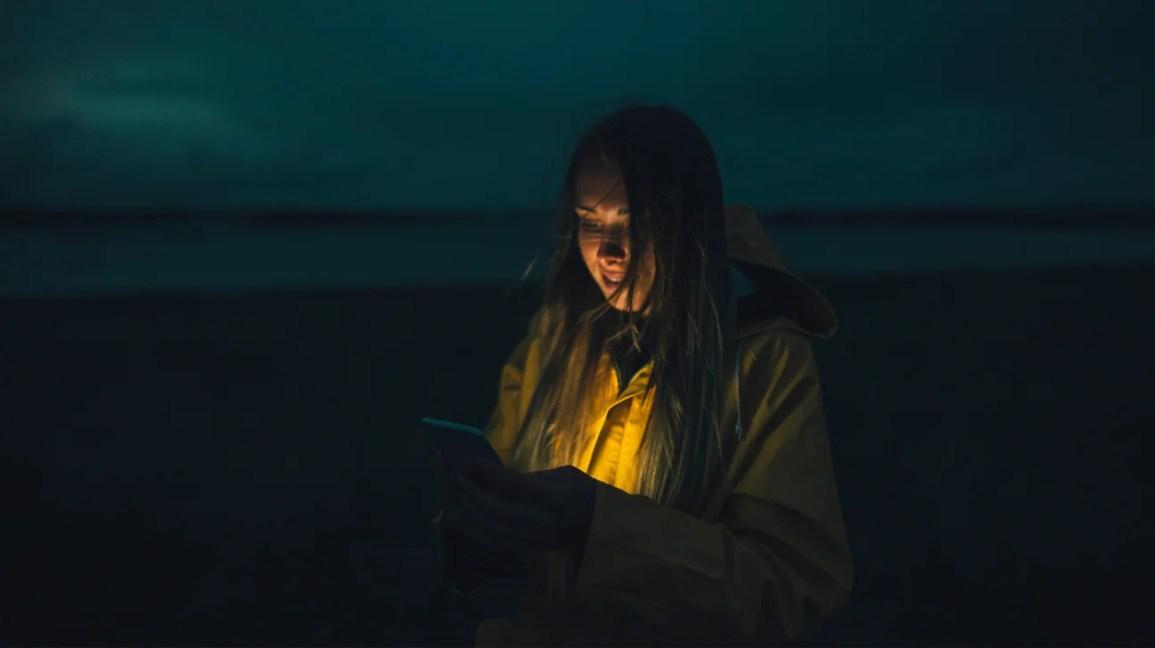pessoa iluminada pelo brilho do telefone celular