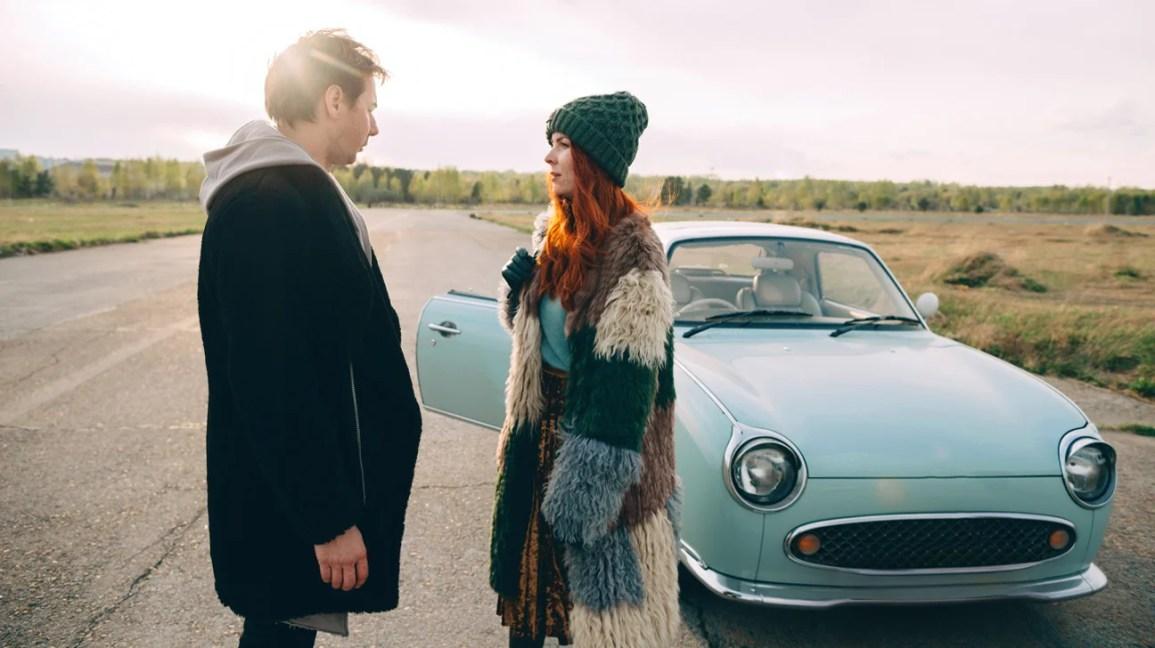 casal discutindo na frente do carro