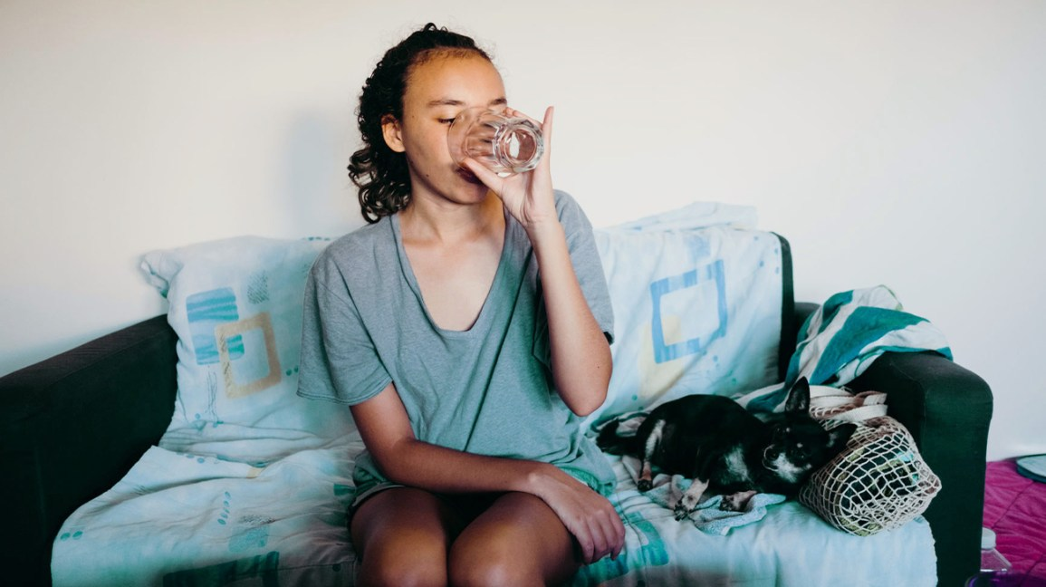 Woman sitting in a sofa drinking water