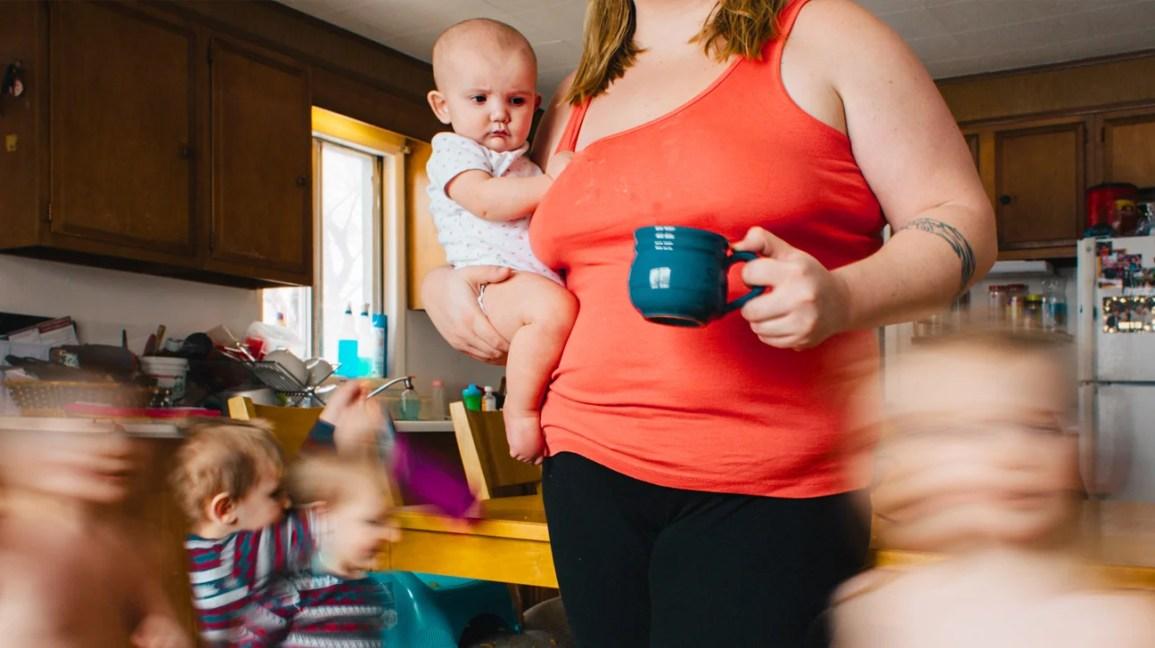 Mãe segurando bebê com crianças correndo sob os pés