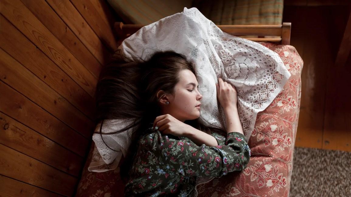 mulher dormindo de lado na cama
