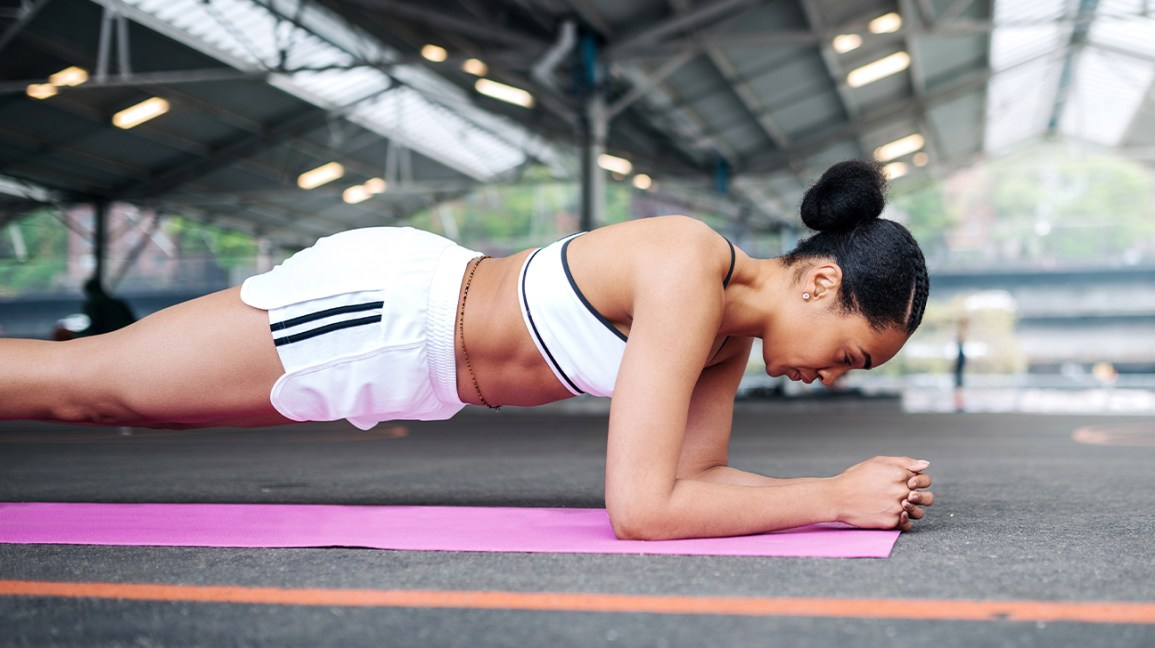 woman in plank position on yoga mat