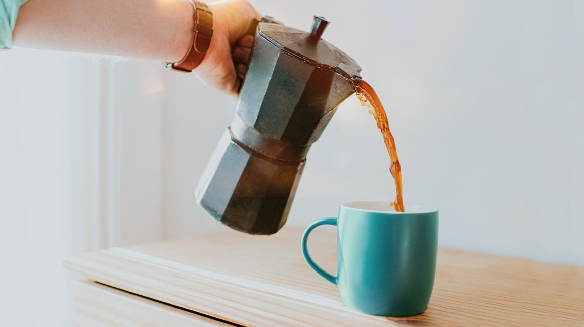 Un uomo si versa una tazza di caffè decaffeinato in una tazza turchese.