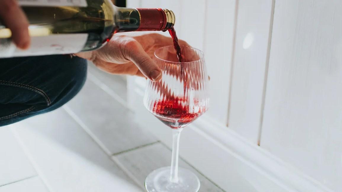kırmızı şarap beyaz tezgahta bardağa dökülüyor