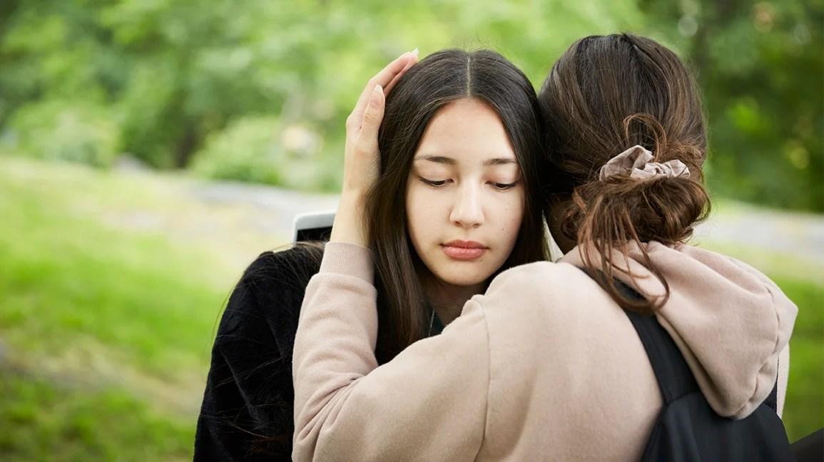 adolescente triste sendo abraçado por um amigo