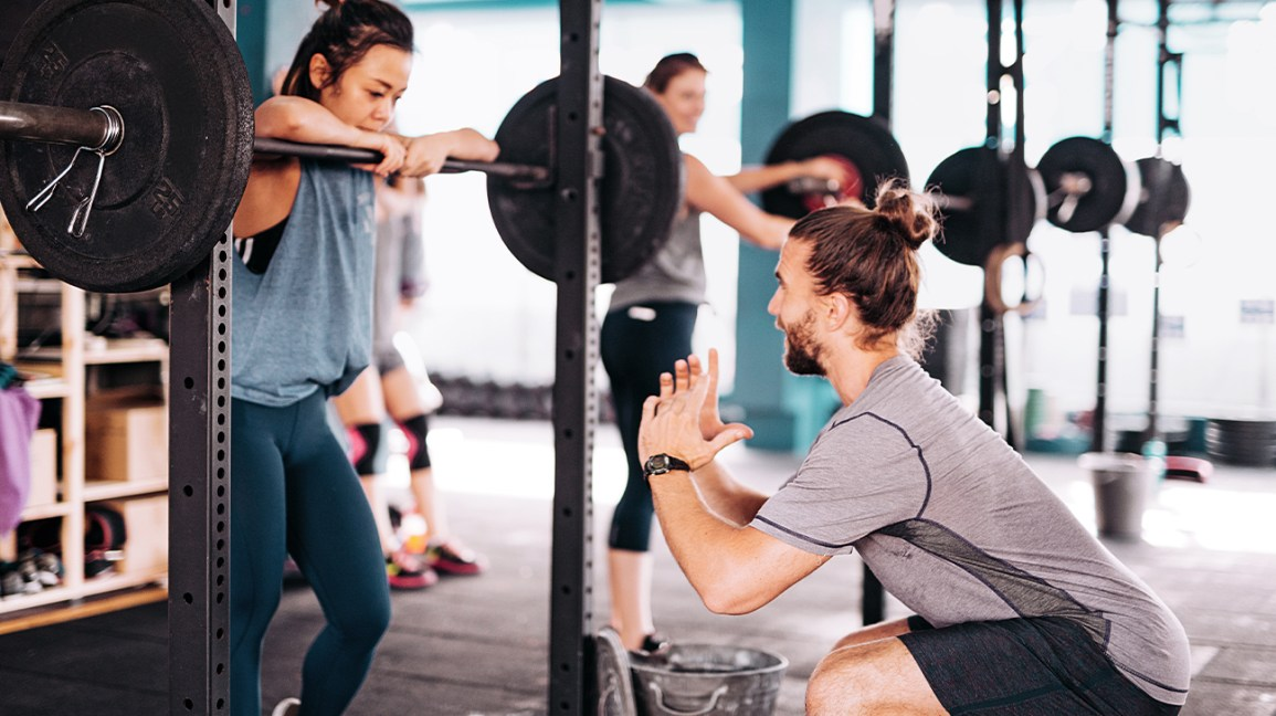 a trainer leading someone in squats