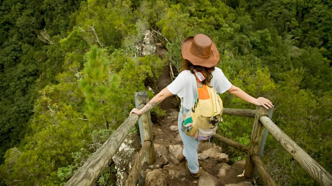Uma mulher está no topo de uma escada externa, olhando para uma floresta.