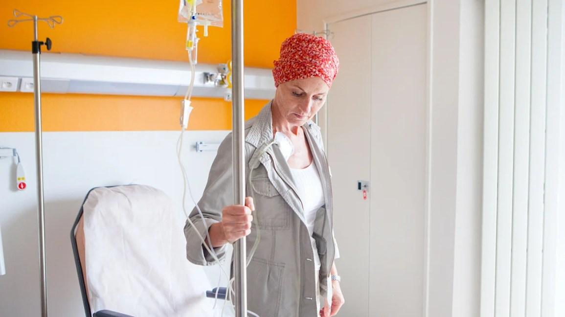 Um paciente de quimioterapia se levanta enquanto recebe uma infusão de quimio em um ambulatório.