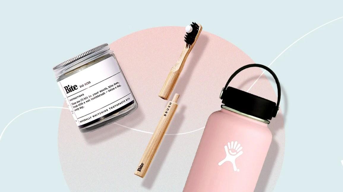 Una selezione di prodotti sostenibili, tra cui pezzetti di dentifricio Bite, uno spazzolino da denti in bambù e una bottiglia d'acqua rosa riutilizzabile, su uno sfondo blu e rosa pastello.