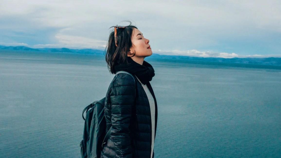 Uma mulher está ao ar livre perto de um grande lago, respirando ar fresco.